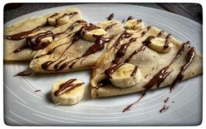Tri palacinky s banánom poliate čokoládou