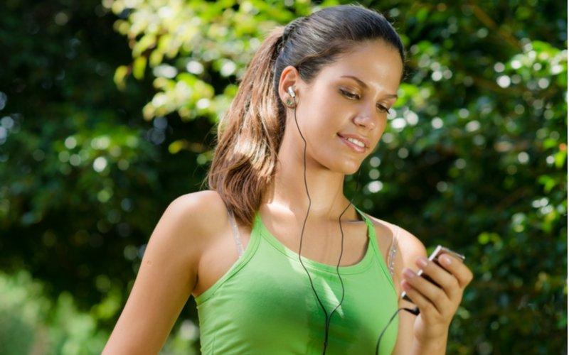 MP3 prehrávač pri športe - mladá žena so zariadením v ruke