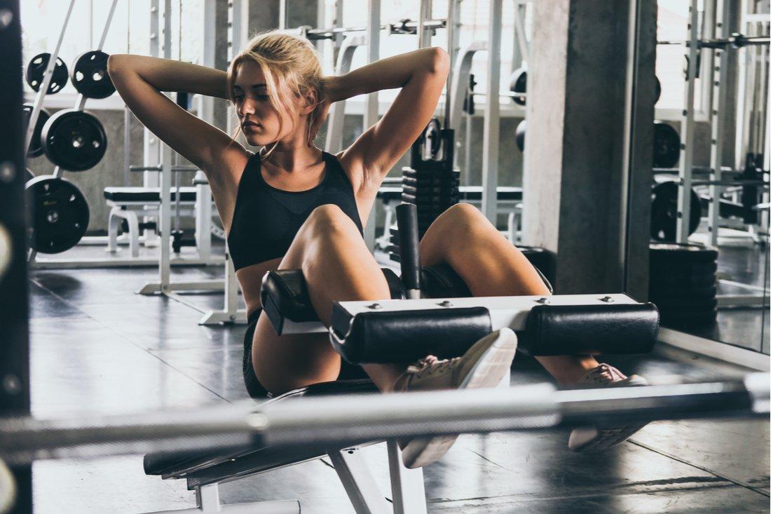 Mladá žena cvičí brušáky v posilňovni