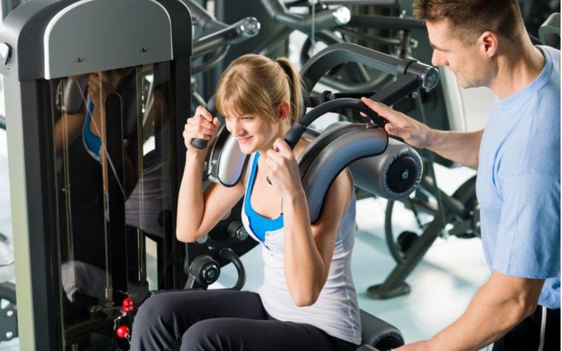 Žena cvičí v posilňovni s trénerom