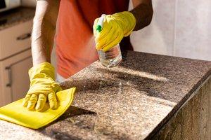 muž v rukaviciach čistiaci kuchynskú pracovnú dosku