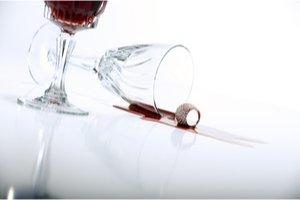 prevrhnutý pohár s červeným vínom