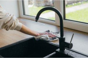 žena utierajúca vodu okolo kuchynského drezu
