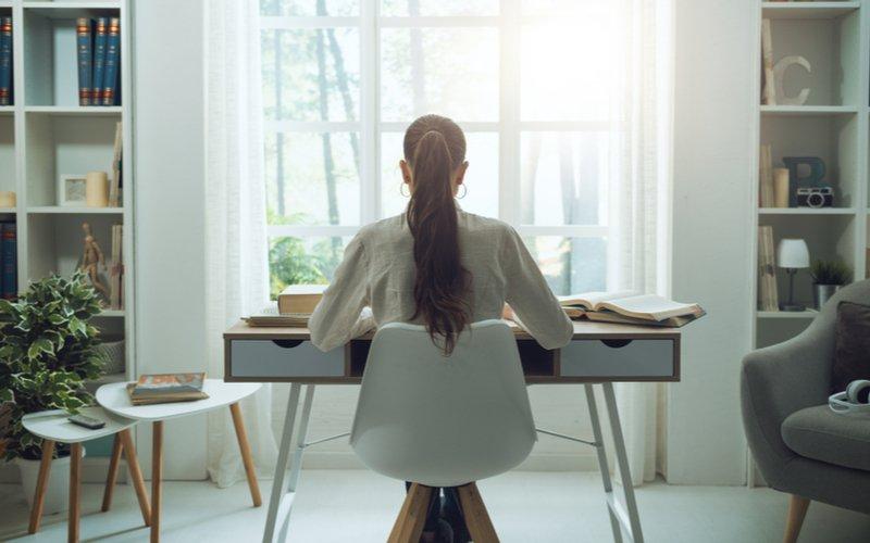 Žena za písacím stolom postaveným pri okne