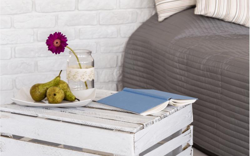 detail spálne s bielym nočným stolíkom z drevenej debničky