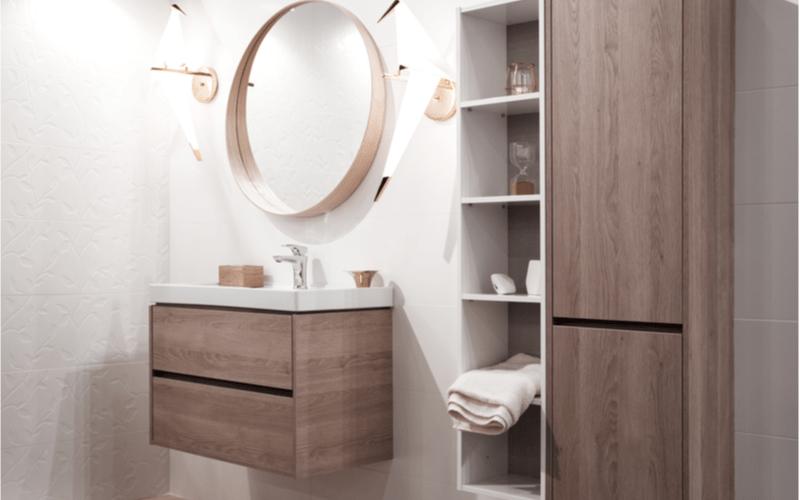 kúpeľňa s bielymi obkladačkami a závesnými skrinkami s dekorom tmavého dreva