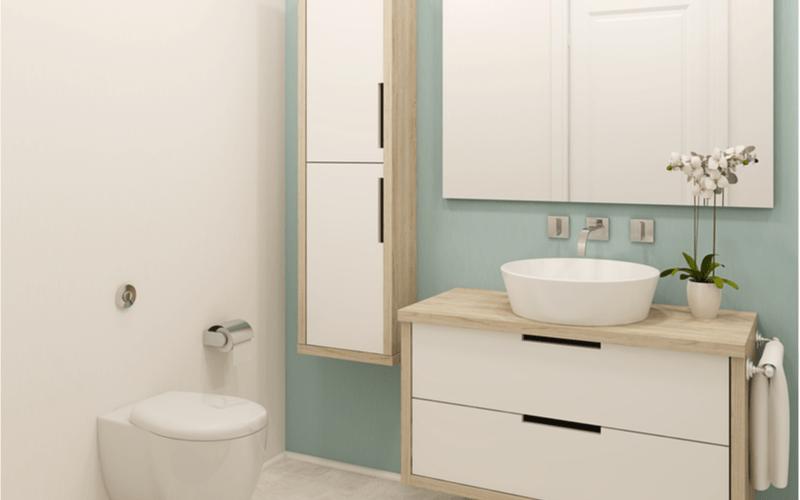 kúpeľňa so stenou mätovej farby s bielymi závesnými kúpeľňovými skrinkami