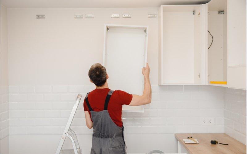 muž montujúci bielu kuchynskú linku na mieru