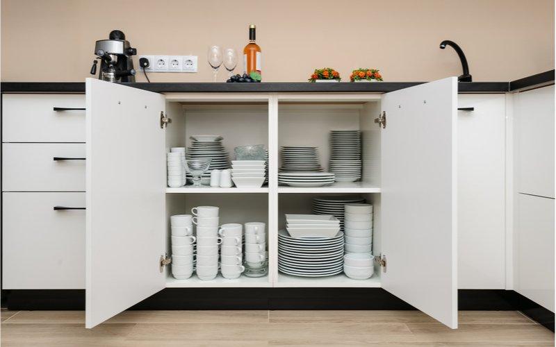 otvorené dvierka na skrinke bielej kuchynskej linky