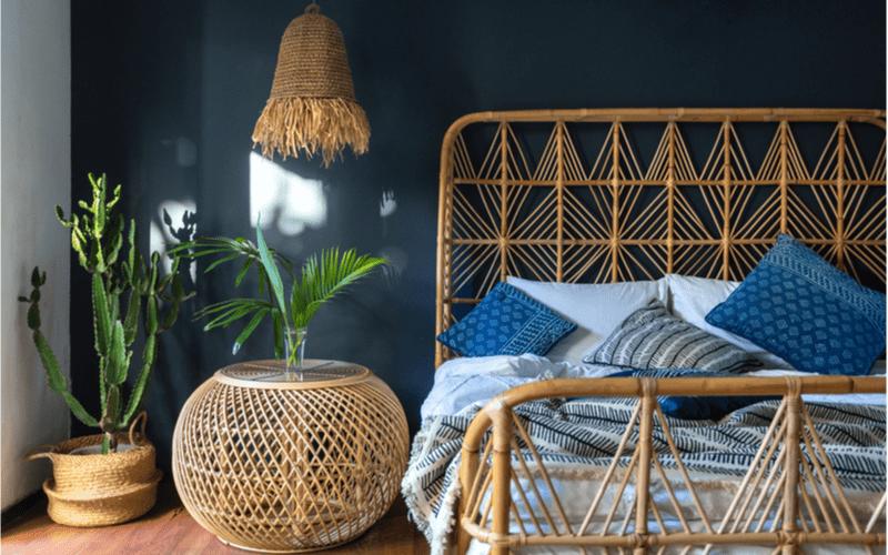 spálňa so stenou petrolejovej farby zariadená s použitím prírodných materiálov - ratanový nočný stolík