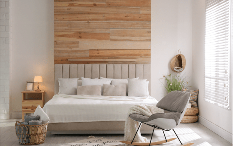 spálňa v svetlých farbách s veľkou posteľou a dreveným nočným stolíkom
