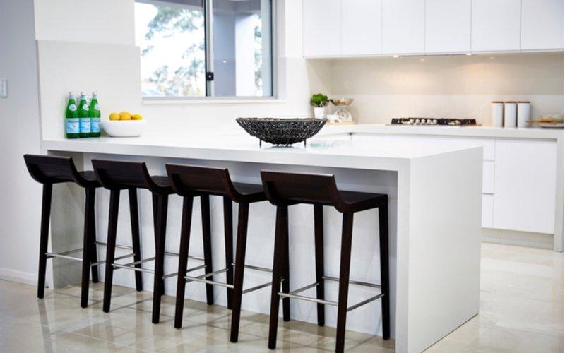 Biela kuchyňa s čiernymi barovými stoličkami