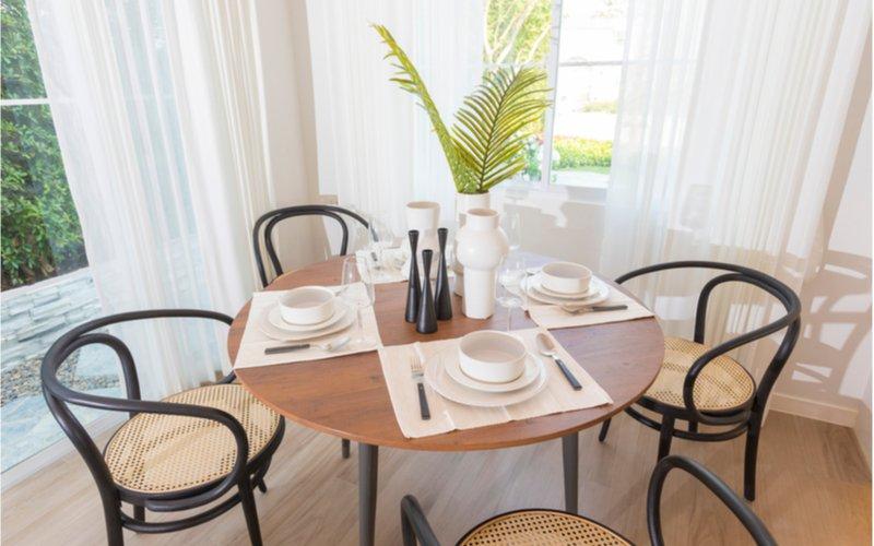 detail na okrúhly jedálenský stôl z masívu s bielym prestieraním a ratanovými stoličkami