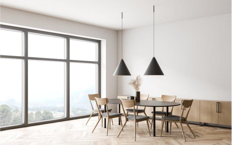 jedáleň s presklenou stenou, oválnym jedálenským stolom a drevenými stoličkami s čalúnením