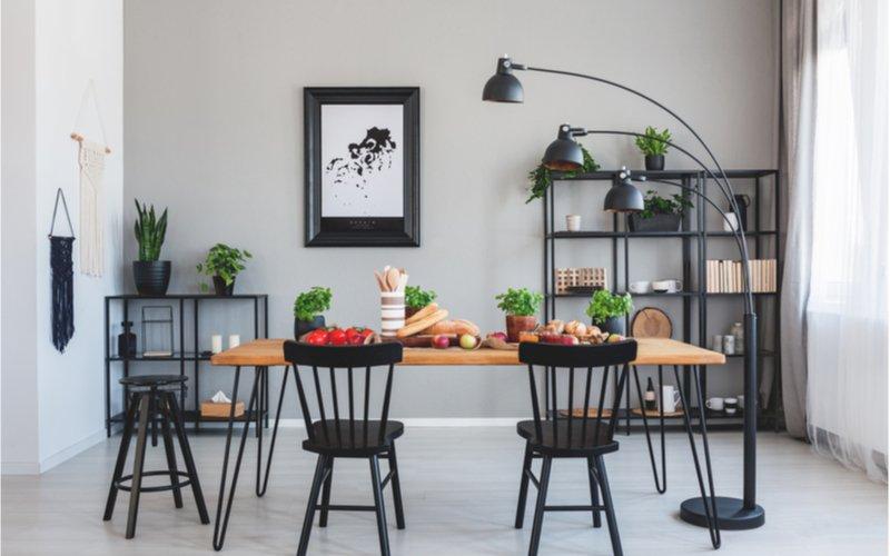 sivá jedáleň s čiernymi policami, dreveným jedálenským stolom a čiernymi stoličkami