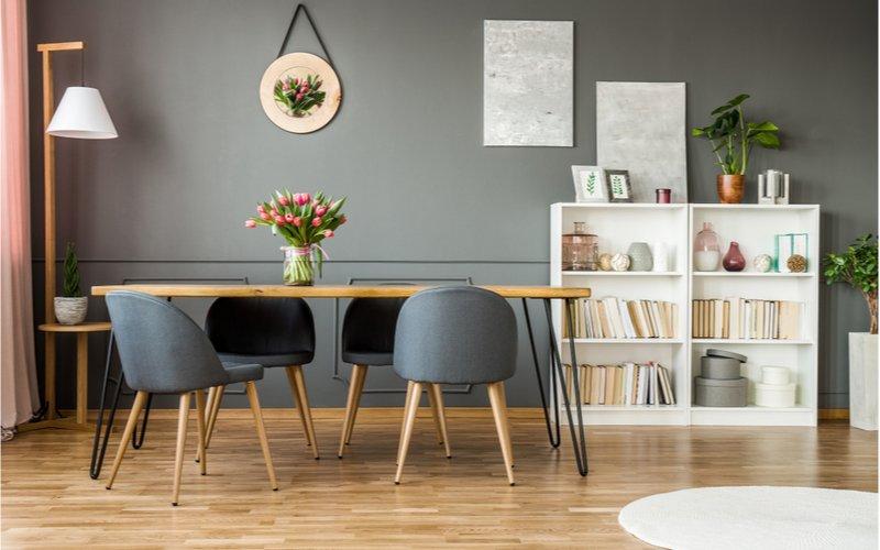 útulný interiér so šedými stenami, obdĺžnikovým jedálenským stolom z masívu a šedými čalúnenými stoličkami