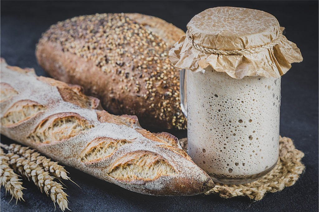 kváskový chlieb a bageta, pohár s kváskom na tmavom pozadí