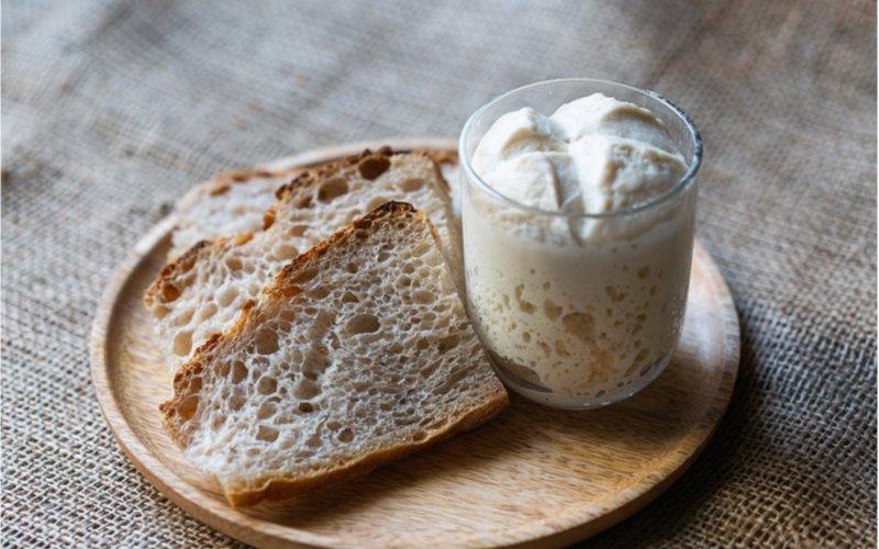 pšeničný kvások lievito madre v pohári, krajce kváskového bieleho chleba